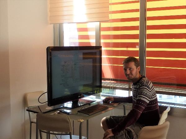 Pete using a massive TV screen to enable him to see the files much easier when proofreading a manuscript